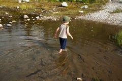 趟过在水中的男孩 免版税库存图片