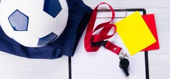足球、体育短裤、一个书写纸、两张刑事卡片和一声口哨在一条红色丝带法官的,灰色背景的 库存图片