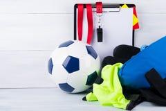 足球、口哨、惩罚卡片和一种片剂记录的一件法官和运动服在一个袋子,在灰色背景 免版税库存图片