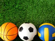 足球、篮球和排球的球在绿草说谎 库存照片