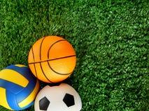 足球、篮球和排球的球在绿草说谎 免版税图库摄影