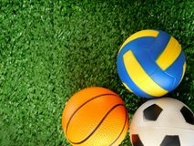 足球、篮球和排球的球在绿草说谎 免版税库存图片