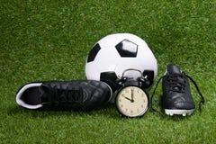 足球、起动和闹钟,在草背景 库存图片