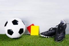 足球、黑起动和两张惩罚卡片法官的,立场在草,在灰色背景 免版税库存图片