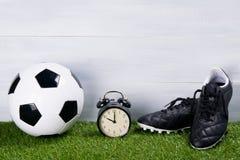 足球、黑起动和闹钟,在草的立场,在灰色背景 图库摄影