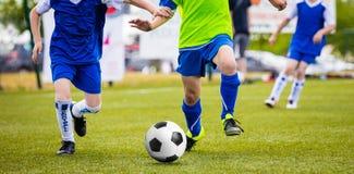 足球儿童青年队的训练比赛 跑在沥青的年轻男孩 图库摄影