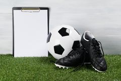 足球和鞋子在草在轻的背景,一个地方您的题字的 图库摄影