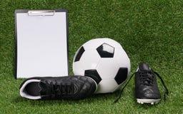 足球和鞋子有一张纸的结果的在绿色草坪说谎 库存照片