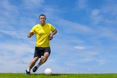 足球在草沥青的足球运动员训练 免版税图库摄影