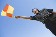 足球巡边员挥动的旗子 免版税库存图片