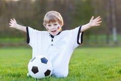 足球或橄榄球赛公开观察的小爱好者男孩  免版税图库摄影