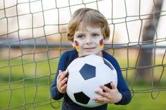 足球或橄榄球赛公开观察的小爱好者男孩  库存图片