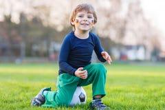 足球或橄榄球赛公开观察的小爱好者男孩  库存照片