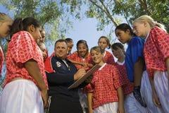 足球教练谈论战略与女孩队 图库摄影