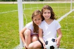 足球橄榄球使用在领域的孩子女孩 免版税库存照片