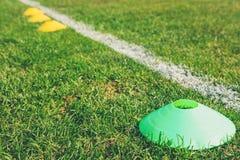 足球橄榄球在绿色领域的训练锥体 库存图片