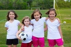 足球橄榄球孩子女孩合作在体育fileld 库存照片