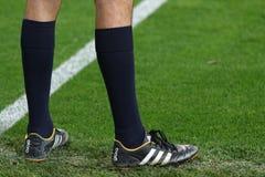 足球裁判员的脚绿草的 库存图片