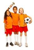 足球赛的愉快的孩子优胜者与得奖的杯子的 免版税库存照片