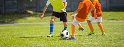 足球足球比赛 踢足球的孩子 踢橄榄球的年轻男孩 免版税图库摄影