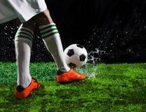 足球踢对在绿草的足球的足球运动员调遣与飞溅透明水反对黑背景 免版税图库摄影
