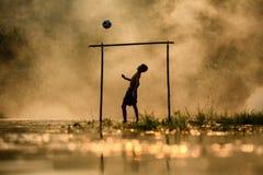足球踢橄榄球的男孩剪影在河 图库摄影
