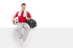 年轻足球运动员坐一个空白的广告牌 免版税图库摄影