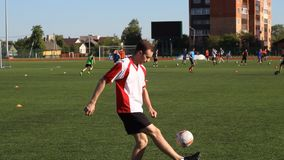 足球运动员是训练和弹起在他的脚的一个足球 股票录像