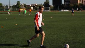 足球运动员是训练和弹起在他的腿的一个足球 股票录像