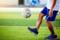 足球运动员跳并且射击球对在人为草皮的目标 免版税库存照片