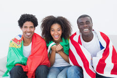 足球迷坐有旗子的长沙发 库存图片