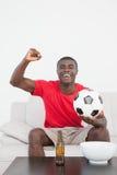 足球迷坐有球欢呼的长沙发 免版税库存图片