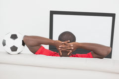 足球迷坐有球的长沙发 库存照片