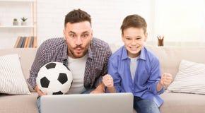 足球迷爸爸和在膝上型计算机的儿子观看的足球比赛在网上 免版税库存图片