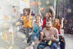 足球迷的愉快的朋友观看在电视的足球和庆祝与落的五彩纸屑的胜利 库存图片