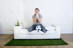 足球迷观看的电视足球比赛痛苦重音祈祷的神 免版税图库摄影