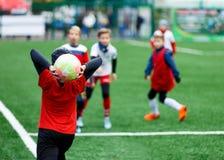 足球队-红色,蓝色,白色一致的戏剧足球的男孩在绿色领域 滴下的男孩 滴下的技能 成队比赛 图库摄影