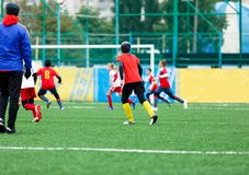 足球队-红色,蓝色,白色一致的戏剧足球的男孩在绿色领域 滴下的男孩 滴下的技能 成队比赛 库存照片