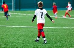 足球队-红色,蓝色,白色一致的戏剧足球的男孩在绿色领域 滴下的男孩 滴下的技能 成队比赛 库存图片