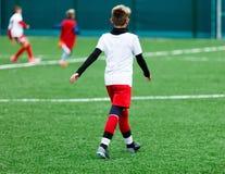 足球队-红色,蓝色,白色一致的戏剧足球的男孩在绿色领域 滴下的男孩 滴下的技能 库存照片