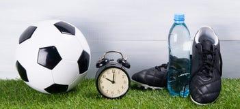 足球,起动,水瓶,闹钟,在草的立场,在灰色背景 库存照片