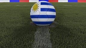 足球/橄榄球经典球在领域草的中心与乌拉圭旗子的绘画的与焦点的总体上调遣, 3 图库摄影