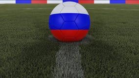 足球/橄榄球经典球在领域草的中心与俄罗斯旗子的绘画的与defocused的景深, 3D的 库存图片