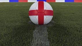 足球/橄榄球经典球在领域草的中心与英国旗子的绘画的与defocused的景深的, 免版税库存图片