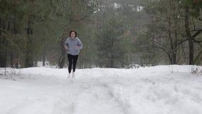 足迹奔跑 跑在雪的森林里的年轻可爱的白种人女孩 前面静态射击 股票录像