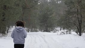 足迹奔跑 跑在雪的森林里的年轻可爱的白种人女孩 r 股票视频