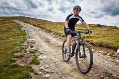 足迹的山骑自行车的人 免版税库存图片
