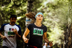 年轻活跃女子运动员在森林,宽松头发里跑 免版税图库摄影