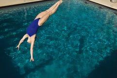 活跃女性游泳者潜水 免版税库存图片