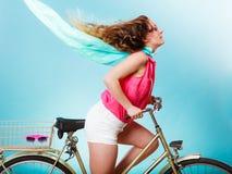 活跃妇女骑马自行车自行车 被风吹的头发 图库摄影